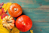 Pumpkins on colorful leaves on green wooden background. Top view. Autumn and Halloween image.