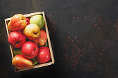 Ripe green and red apples with pears in a wooden box on dark background. Autumn seasonal image with top view.