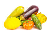 Vegetarian healthy food with vegetables. Tomatoes, cucumbers, bush pumpkins, eggplants and marrows isolated on white background.