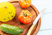 Salad delicatessen preparation. Vegetarian healthy food. Tomatoes, cucumber and bush pumpkin on cutting board with knife on blue wooden background.