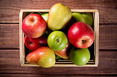 Ripe apples and pears in a wooden box on dark brown wooden rustic background. Autumn seasonal image with top view.