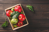 Ripe green and red apples in a wooden box with leaves on dark brown wooden rustic background. Autumn seasonal image with top view.