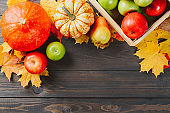 Pumpkins with colorful maple leaves, ripe apples in a box and pear on dark wooden background. Autumn seasonal image with free space for your text