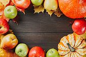 Pumpkins with colorful maple leaves, ripe apples and pear on dark wooden background. Autumn seasonal image with free space for your text