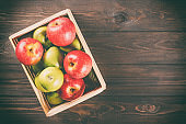 Ripe green and red apples in a wooden box on dark brown wooden rustic background. Autumn seasonal image with top view.