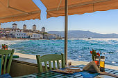 Mykonos, panoramic view of white famous windmills  Chairs with tables in typical Greek restaurant  of Little Venice in Cyclades island, Greece.