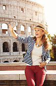 traveller woman in front of Colosseum taking selfie with phone