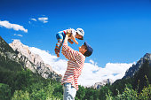 Mother and baby with mountains on a background. Family spend summer holiday in Dolomites, South Tyrol, Italy, Europe.
