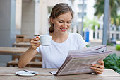 Happy young woman drinking coffee and reading newspaper at cafe