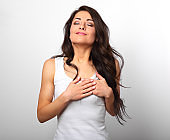 Beautiful woman in love holding herself chest and heart two hands with enjoying smiling face and thinking about emotion relationship on white background