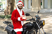 Cheerful Christmas biker delivering gifts