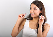 Happy smiling woman cleaning the teeth the dental floss on blue background with empty copy space. Dental Hygiene. Closeup