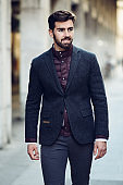 Young bearded man smiling in urban background wearing british elegant suit in the street.