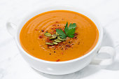 soup of pumpkin and lentils on white background, closeup