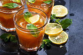 refreshing iced tea with mint and lemon on dark background