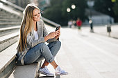 Beautiful young blonde woman looking at her smartphone and smiling.