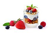 Berry fruit parfait in a mason jar with scattered fruit isolated on white