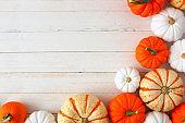 Autumn corner border of varied pumpkins on white wood, top view