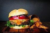 Hamburger with potato wedges on dark background