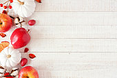 Red and white autumn side border with apples & pumpkins on white wood