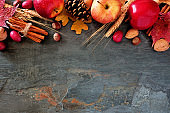 Autumn top border of apples, fall foods & decor on dark stone