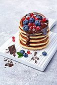 Homemade pancakes with fresh blueberry, cranberry and chocolate cream on white wooden cutting board