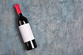 Flat lay of lying red wine bottle with white empty label