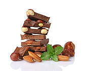 Close-up pieces of chocolate bar with whole almonds and mint