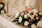 Wedding reception details, wedding dinner, tables, and flowers close up with depth of field