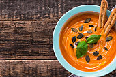 Roasted pumpkin and carrot soup with cream and pumpkin seeds