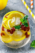 Cold and refreshing detox water infused with lemon, cranberries and mint in a glass with ice cubes. lemonade. Healthy beverage. Selective focus