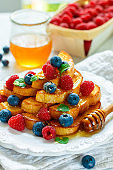 Traditional Breakfast - French toast with honey and fresh berries - raspberries and blueberries in a white plate on the table
