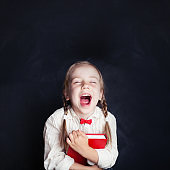 Happy little girl laughing. Happy child with red book on empty blackboard background with copy space. Back to school concept.