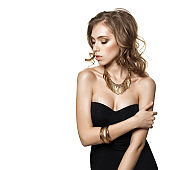 Beautiful Young Woman Fashion Model with Wavy Brown Hair and Gold Jewelry Necklaces Isolated on White Background