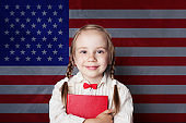 English concept with little girl student with book against the UK flag background. Learn language