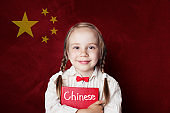 Chinese concept. Little girl student with book against the Chinese flag background. Learn language
