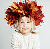 Cute little girl with autumn leaves on background with copy space