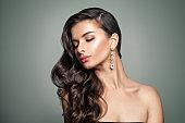Beautiful Female Model. Perfect Makeup. Wavy Hair. Jewelry Earrings