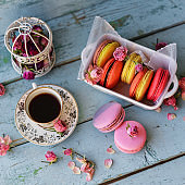 Dessert With Coffee: A Delicate Fresh French Macaroons In Pastel Colors Gift Box Flowers Roses On Light Blue Wooden Background