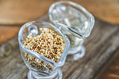 sesame seed oil and sesame seed oil in glass Cup on natural wooden background, healthy food concept, organic food.