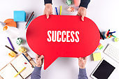 Two people holding speech bubble with SUCCESS concept
