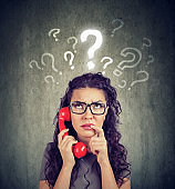Upset worried confused woman talking on a phone has many questions