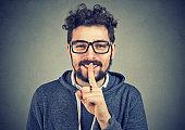 Smiling man holding finger on lips