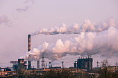 smoke stacks in a working factory emitting steam, smog and air pollution.