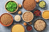 Vegetarian protein sources: legumes, cereals, spinach, spices, nuts. Healthy balanced meal. Top view, flat lay.