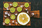 Slices of lime and pomelo with ice cubes on a cutting board. Refreshing citrus fruits. View from above.