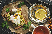 A fresh breakfast of poached egg, avocado sandwich and lemon tea on a black wooden rustic tray. Top view, flat lay.