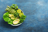Detox Buddha bowl with avocado, asparagus, micro greens, lime, lettuce, basil and mint.Dietary food. Blue rustic background, top view.
