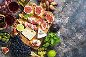 A variety of appetizer, prosciutto,grapes, wine, cheese with mold, figs, olives on a rustic background. Mediterranean snack.Top view,flat lay,copy space.