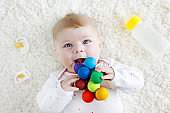 Cute baby girl playing with colorful wooden rattle toy, nursing bottle and dummy